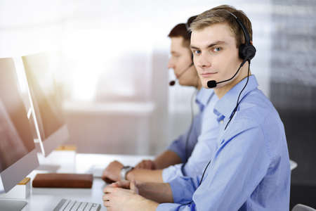 Two young men in headset, sitting at the desk in a sunny modern office, listening to the clients. Call center operators at work
