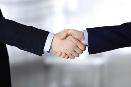 Business people shaking hands, close-up. Group of unknown businessmen standing in a modern office. Teamwork, partnership and handshake concept