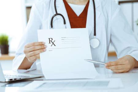 Unknown woman-doctor pointing into empty prescription form record close-up. Medicine concept