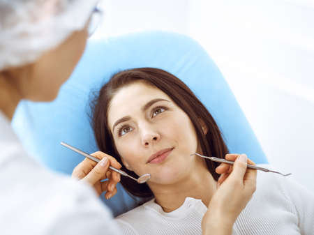 Smiling brunette woman being examined by dentist at dental clinic. Hands of a doctor holding dental instruments near patients mouth. Healthy teeth and medicine concept