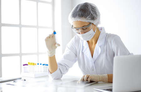 Professional female scientist in protective eyeglasses researching tube with reagents in laboratory. Concepts of medicine and research.