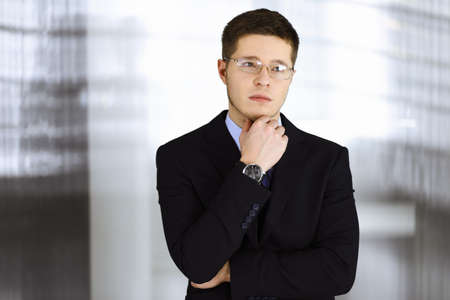 Young businessman wearing suit, with glasses, while standing in the office. Business success concept nowadays