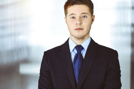 Young businessman in a suit, while standing in a sunny office. Business success concept nowadays