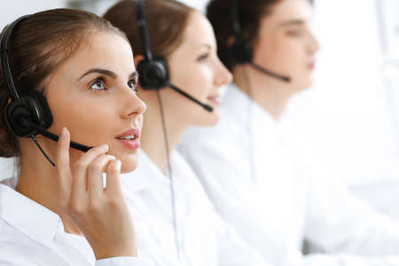 Call center. Beautiful young woman using headset and computer to help customers. Business concept