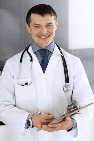 Doctor man using clipboard for filling up medication history records. Perfect medical service in clinic. Physician at work in hospital. Medicine and healthcare concepts Imagens