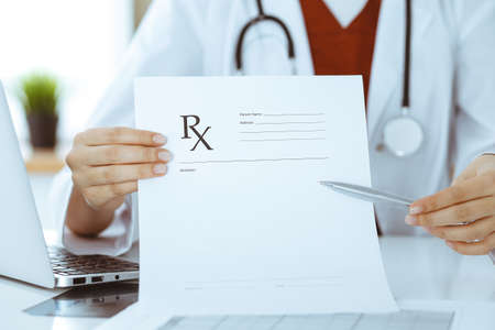 Unknown woman-doctor pointing into empty prescription form record close-up. Medicine concept Stock Photo