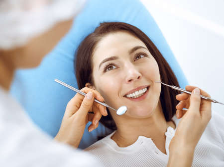 Smiling brunette woman being examined by dentist at dental clinic. Hands of a doctor holding dental instruments near patients mouth. Healthy teeth and medicine concept Stock Photo