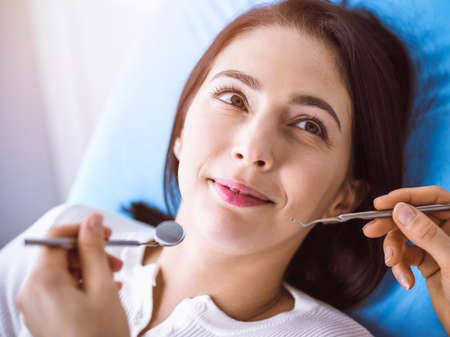 Smiling brunette woman being examined by dentist at sunny dental clinic. Hands of a doctor holding dental instruments near patients mouth. Healthy teeth and medicine concept Reklamní fotografie