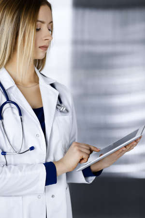 Young professional woman-doctor is using a tablet computer, while standing in a clinic. Portrait of beautiful female physician at work. Perfect medical service in hospital. Medicine concept Zdjęcie Seryjne
