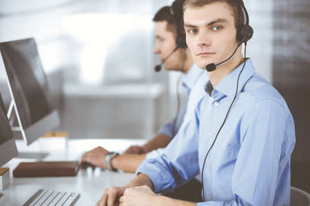 Two young men in headset, sitting at the desk in the modern office, listening to the clients. Call center operators at work