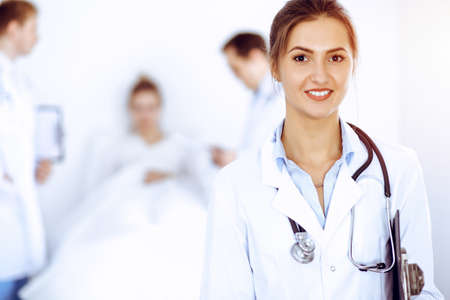 Female doctor smiling on the background with patient in the bed and two doctors