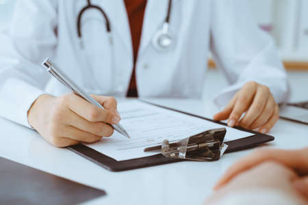 Unknown woman-doctor filling up an application form while consulting patient. Medicine concept