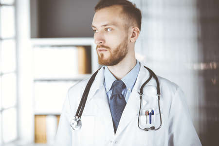 Red-bearded doctor standing straight in clinic near his working place. Portrait of physician. Medicine and healthcare concept Foto de archivo