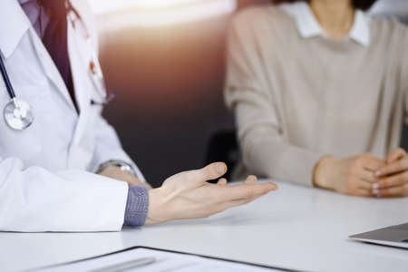 Unknown male doctor and patient woman discussing something while sittingin a darkened clinic, glare of light on the background. Close-up of hands Banque d'images