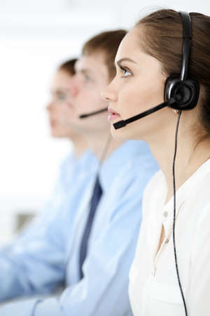 Call center. Diverse customer service operators in headsets at work in office. Business concept
