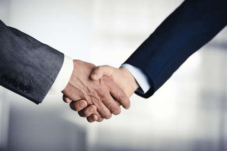 Business people in office suits standing and shaking hands, close-up. Business communication concept. Handshake and marketing Banco de Imagens