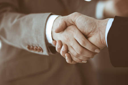 Business people shaking hands while standing with colleagues after meeting or negotiation, close-up. Group of unknown businessmen and women in modern office. Teamwork, partnership and handshake concept, toned picture. Archivio Fotografico
