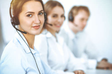 Call center. Focus on beautiful business woman in headset