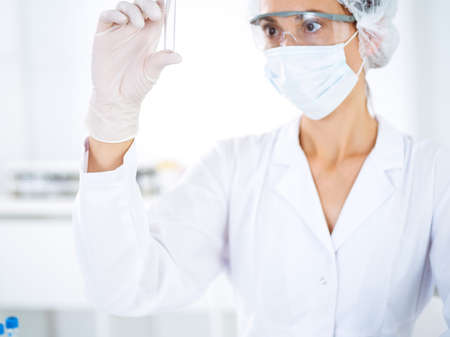 Professional female scientist in protective eyeglasses researching tube with reagents in laboratory. Concepts of medicine and science researching