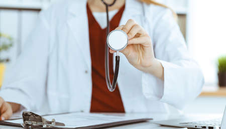 Unknown woman-doctor with a stethoscope in the hands. Physician is ready to examine a patient, close-up of hands. Medicine concept Stok Fotoğraf