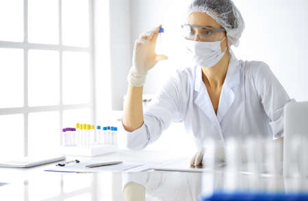 Professional female scientist in protective eyeglasses researching tube with reagents in sunny laboratory. Medicine and researching