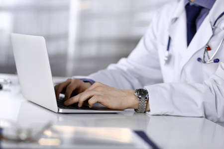 Unknown male doctor sitting and working with laptop in clinic at his working place, close-up. Young physician at work. Perfect medical service, medicine concept Stockfoto