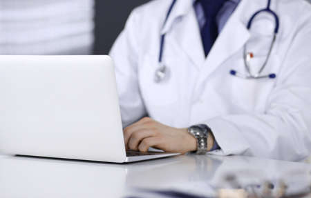 Unknown male doctor sitting and working with laptop in clinic at his working place, close-up. Young physician at work. Perfect medical service, medicine concept Stock Photo