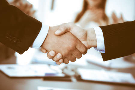 Business people shaking hands at meeting while theirs colleagues clapping and applausing. Group of unknown businessmen and women in modern white office. Success teamwork, partnership and handshake concept. Banque d'images