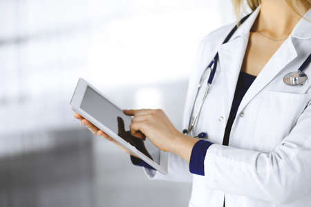 Unknown woman-doctor is holding a tablet computer in her hands, while standing in a clinic cabinet. Female physician at work, close-up. Perfect medical service in a hospital. Medicine concept
