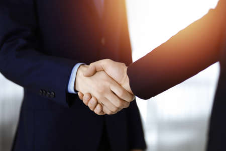 Business people shaking hands, close-up. Group of unknown businessmen standing in a sunny modern office. Teamwork, partnership and handshake concept