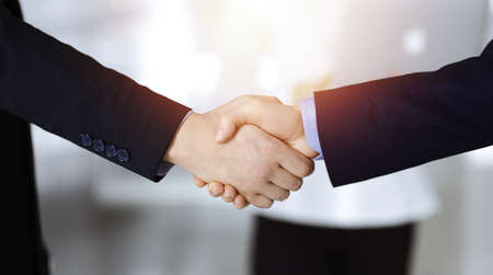 Business people shaking hands at meeting or negotiation, close-up. Group of unknown businessmen and a woman stand together in a sunny modern office. Teamwork, partnership and handshake concept Stockfoto