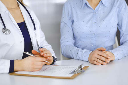 Unknown woman-doctor is writing down on her papers patient's symptoms of a cold, while sitting together at the desk in the cabinet in a clinic. Female physician is using a clipboard and a stethoscope, close up. Perfect medical service in a hospital. Medicine concept. Stockfoto