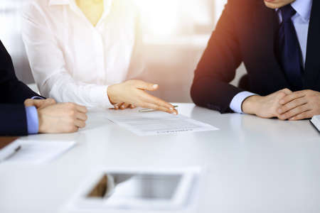 Group of business people, men and a woman, discuss details of a contract at meeting in a sunny modern office. Discussion at negotiation or workplace. Teamwork, partnership and business concept Stock Photo