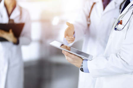 Group of unknown doctors  use a computer tablet to check up some medical names records, while standing in a sunny hospital office. Physicians ready to examine and help patients. Medical help, insurance in health care, best desease treatment and medicine concept.