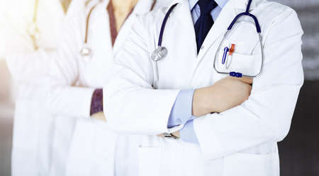 Group of modern doctors standing as a team with crossed arms and stethoscopes in a sunny hospital office. Physicians ready to examine and help patients. Medical help, insurance in health care, best desease treatment and medicine concept.