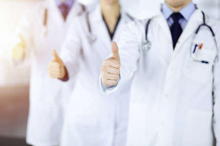 Group of unknown doctors stand as a team with thumbs up in a sunny hospital office. Physicians ready to examine and help patients. Medical help, insurance in health care, best desease treatment and medicine concept.