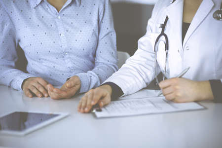 Unknown woman- doctor is listening to her patient, while sitting together at the desk in the cabinet in a clinic. Female physician with a stethoscope is writing at clipboard, close up. Perfect medical service in a hospital. Medicine concept.