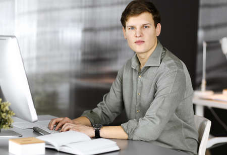 Young successful businessman and programmer in a green shirt is looking at camera, while he is working on his computer, sitting at the desk in a cabinet. Headshot or business portrait in an office