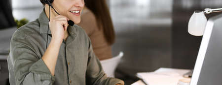 Young dark-haired guy in a green shirt and headsets is talking to a client, while sitting at the desk, working together with a female colleague in a modern office. Call center operators at work