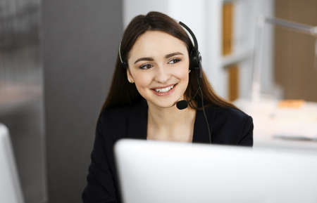 Young friendly girl in headsets is talking to a firms client, while sitting at the desk in a modern office together with her colleague. Call center operators at work Standard-Bild