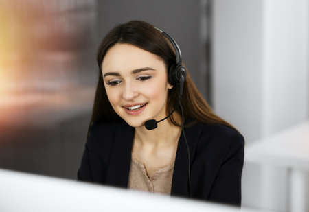 Young friendly girl in headsets is talking to a firms client, while sitting at the desk in sunny office. Call center operators at work