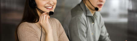 Two young people in headsets are talking to the clients, while sitting at the desk in an office. Focus on woman. Call center operators at work