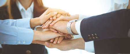 Business team showing unity with their hands together in sunny office. Group of people joining hands and representing concept of friendship, teamwork and partnership Imagens