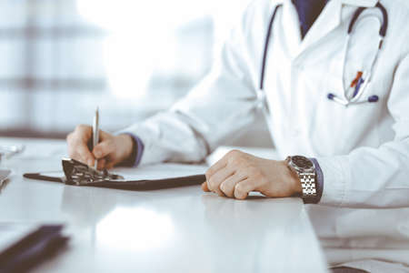 Unknown male doctor sitting and working with clipboard of medication history record in clinic at his working place, close-up. Young physician at work. Perfect medical service, medicine concept