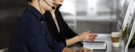 Two young people in headsets are talking to the clients, while sitting at the desk in a modern office. Focus on man in a blue shirt. Call center operators at work
