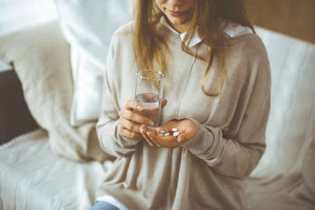 Close-up woman holding pills time to take medications, cure for headache, high blood pressure or cholesterol level remedy pain killer drugs. 免版税图像