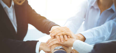 Business team showing unity with their hands together in sunny office. Group of people joining hands and representing concept of friendship, teamwork and partnership Banque d'images
