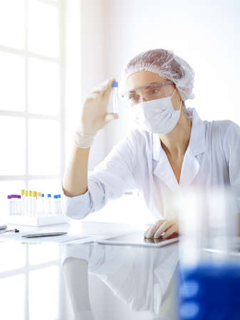 Professional female scientist in protective eyeglasses researching tube with reagents in sunny laboratory. Medicine and science researching Imagens