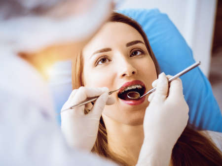 Smiling young woman with orthodontic brackets examined by dentist in sunny dental clinic. Healthy teeth and medicine concept