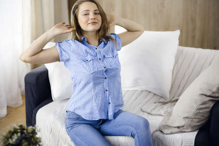 Happy blond woman put hands behind head sitting leaned on couch caucasian female enjoy lazy weekend or vacation in cozy living room, housewife relaxing feels satisfied accomplish chores housework